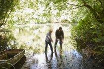 Батько і син риболовля сітками в лісі ставок — стокове фото
