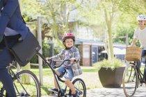 Портрет улыбающийся мальчик в шлеме на тандеме велосипеде с отцом в парке — стоковое фото