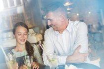 Father and daughter drinking lemonade at cafe table — Stock Photo