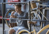 Young man texting with cell phone near bicycles at railing — Stock Photo