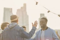 Young men high fiving at rooftop party — Stockfoto