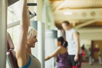 Smiling woman with arms raised using exercise equipment at gym — Stock Photo