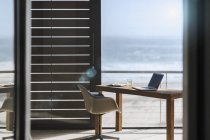 Desk and chair in modern home office overlooking ocean — Stock Photo