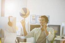 Geschäftsmann Spinnen Basketball am Finger im Büro — Stockfoto