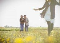 Жінки дивляться дівчина запустити в сонячний луг з польових квітів — стокове фото