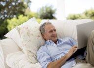 Senior man using laptop on patio sofa — Stock Photo