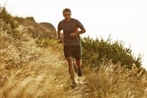Hombre corriendo en el camino a través de hierba alta - foto de stock