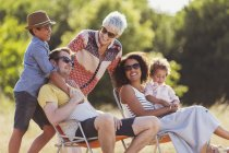 Multi-generation family relaxing in sunny field — Stock Photo
