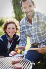 Portrait smiling father and son barbecuing — Stock Photo