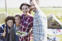 Portrait smiling family with barbecued hamburgers at sunny campsite — Stock Photo