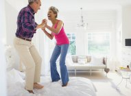 Playful mature couple jumping on top of bed — Stock Photo