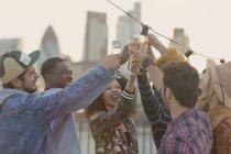 Молодих дорослих друзями тостів шампанського келихи на даху партії — стокове фото