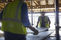 Construction workers lifting plyboard at construction site — Stock Photo