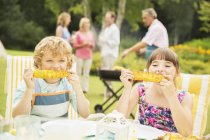 Happy children eating at table in backyard — Stock Photo