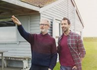 Padre haciendo un gesto a su hijo fuera de casa - foto de stock