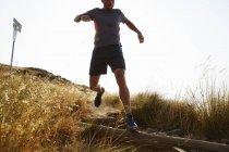 Male runner descending trail hillside — Stock Photo
