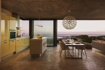 Modern kitchen and dining room overlooking ocean at sunset — Stock Photo