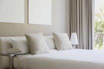 Lit blanc à l'intérieur de la chambre à coucher moderne — Photo de stock