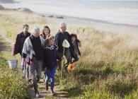 Famiglia multi-generazione a piedi con reti e secchio sul sentiero di spiaggia di erba soleggiata — Foto stock