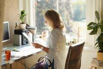 Femme buvant du café et lisant la paperasse au bureau dans le bureau à domicile ensoleillé — Photo de stock