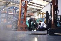 Mecânica trabalhando perto de empilhadeira em oficina de reparação automóvel — Fotografia de Stock