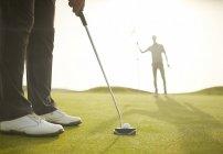 Recorta la imagen del hombre poniendo en el campo de golf - foto de stock
