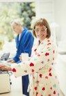 Porträt lächelnd Reife Frau im Bademantel am Küchentisch Kaffee trinken — Stockfoto