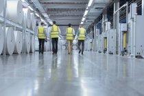 Робітники в світловідбиваючого одяг, Проходячи повз великих Шпулі паперові в поліграфічний комбінат — стокове фото