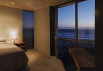 Modernes Schlafzimmer mit Blick auf das Meer in der Abenddämmerung — Stockfoto