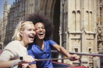 Enthusiastic friends laughing on double-decker bus in London — Stock Photo