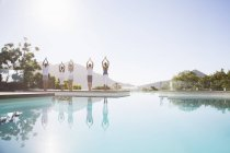 Young attractive people practicing yoga at poolside — Stockfoto