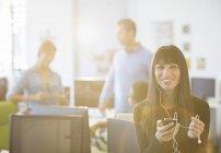 Femme d'affaires à l'écoute du lecteur mp3 dans le bureau — Photo de stock