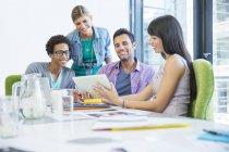 Деловые люди, использующие цифровой планшет на встрече в современном офисе — стоковое фото