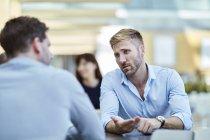 Homme d'affaires gestuelle et parler à un collègue — Photo de stock