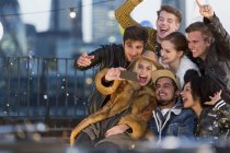 Enthusiastic young adult friends taking selfie at rooftop party — Stockfoto