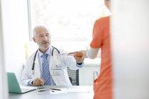 Врач за столом дает медкарту медсестре в кабинете доктора? — стоковое фото