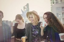 Smiling young women drinking and laughing at rooftop party — Stockfoto