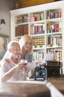 Senior couple drinking wine at typewriter — Stock Photo