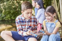 Brother and sister assembling toy wooden raft — Stock Photo