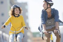 Young couple with helmets riding bicycles in city — Stock Photo