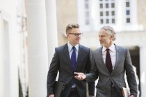 Businessmen talking outdoors against building — Stock Photo