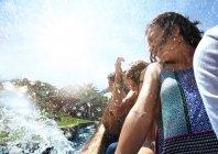 Mulheres jovens ser atingidas no parque aquático cavalgar — Fotografia de Stock