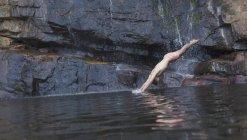 Человек, нырять в озеро против рок — стоковое фото