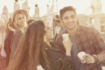 Young adult friends drinking and laughing at rooftop party — Stockfoto
