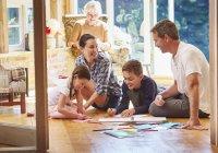 Family coloring on floor in sun room — Stockfoto