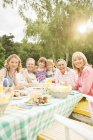 Multi-generation family eating lunch at table in backyard — Stock Photo