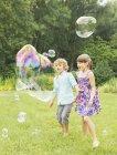 Bambini che giocano con le bolle in cortile — Foto stock