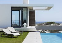Lounge chairs and lap pool outside modern house overlooking ocean — Stock Photo