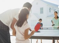 Family playing table tennis outside house — Stock Photo