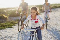 Family riding bicycles on sunny beach — Stock Photo